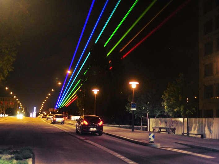"""When artist Yvette Mattern wanted to display her """"Global Rainbow"""" art project in Nantes, France, she turned to Lightwave International to provide the laser skills necessary to bring her vision to life. Utilizing custom-made optics, Lightwave's skilled technicians created a laser rainbow visible from over 60 kilometers away from the city!"""